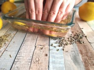 hands in herbal DIY nail soak with lemon