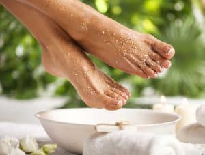 women's feet with exfoliant over foot bath