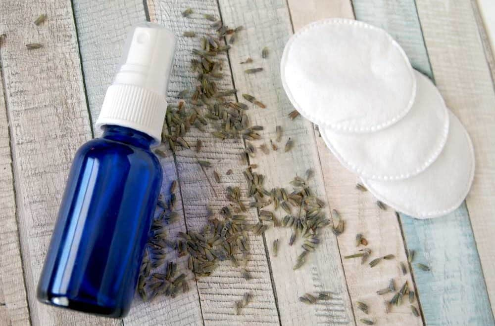 Homemade facial toner in blue bottle with cotton pads